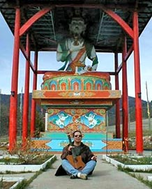 Craig Chaquico seated beneath 40 ft Tibetan Buddha statue at monastery